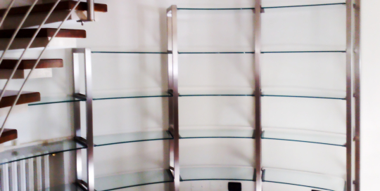 Libreria in acciaio con ripiani in vetro realizzata su una parete curva