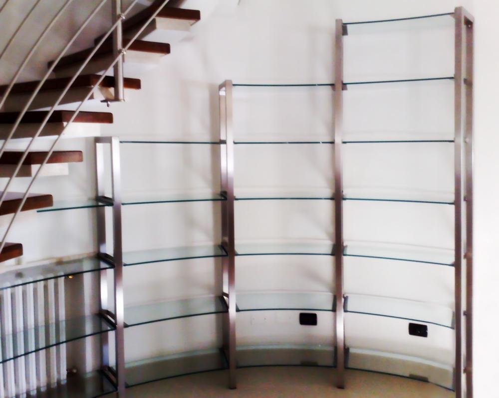 Libreria in acciaio con ripiani in vetro realizzata su una parete ...