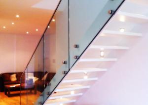 Scala in ferro verniciato con gradini in legno e ringhiera in vetro